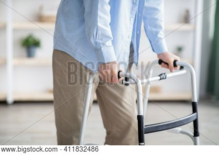 Cropped View Of Elderly Man Walking With Frame At Home, Closeup. Unrecognizable Senior Male Using Me