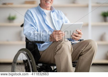 Cropped View Of Disabled Senior Man In Wheelchair Using Tablet Computer For Online Communication At