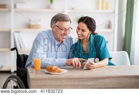 Disabled Senior Man And Young Nurse Using Smartphone Together, Browsing Web Or Watching Movie Indoor