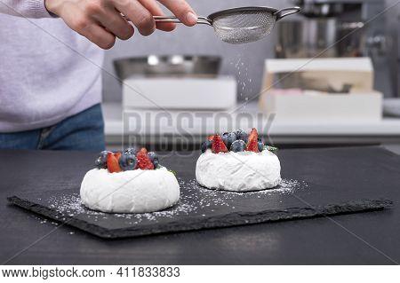 Pastry Chef Sprinkles Icing Sugar On Berry Cakes. Cakes Anna Pavlova