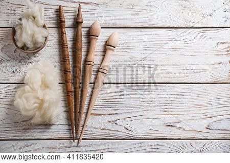 Soft Wool And Spindles On White Wooden Table, Flat Lay. Space For Text