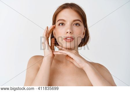 Skin Care And Beauty. Natural Young Woman Standing Naked, Touching Glowing Face. Girl Showing Skinca
