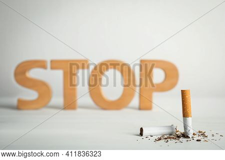 Broken Cigarette Near Word Stop On White Table. Quitting Smoking Concept