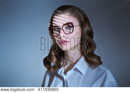 Portrait of a beautiful young businesswoman in elegant glasses and white shirt on grey blue background with shadows. Glasses fashion. Business style.