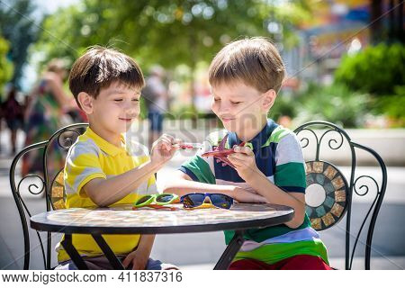 Two Little Kid Boys Waiting On Table For Healthy Breakfast In Hotel Restaurant Or City Cafe. Child S