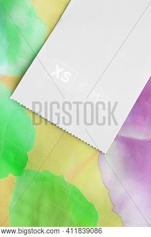 Size Xs Clothing Label On Colorful Textile Background Closeup