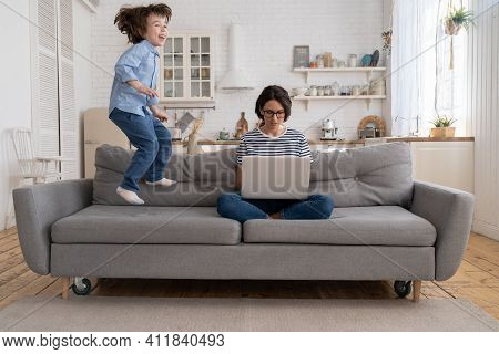 Focused Young Mother Freelancer Wear Glasses Sitting On Couch Working On Laptop At Home, Trying To C