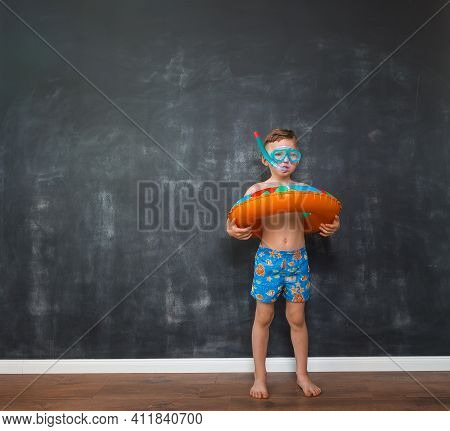 Cute Little Boy Laughs In Bright Colorful Swimming Trunks With Fishes Print On It. Boy With Orange I