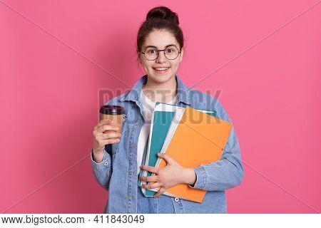 Smiling Young European Student Girl Holds Folders Wears Denim Jacket. Pleased Female With Dark Hair