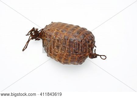 Smoked Ham In One Piece, Isolated On A White Background. Homemade, Smoked Cold Cuts, In Netting. Tra