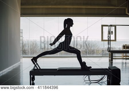 Fit Female Coach Practicing Pilates Exercises Routine On A Reformer Bed Machine, Slim Woman Working