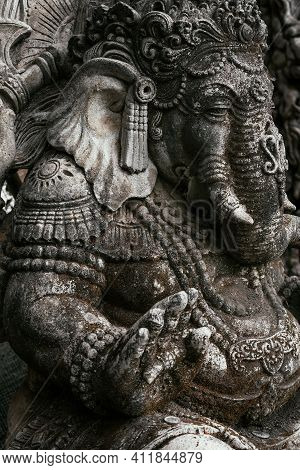 Close-up Of An Ancient Sculpture In Indonesia On The Island Of Bali. Grey Stone Sculpture In The Old