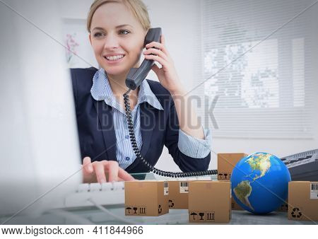 Composition of cardboard boxes with globe and businesswoman talking on phone and using computer. global shipment and delivery concept digitally generated image.