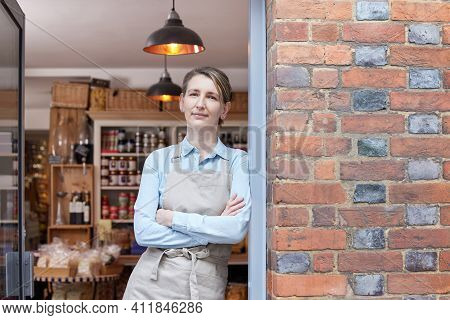 Portrait Of Female Owner Standing In Doorway Of Delicatessen  Food Shop