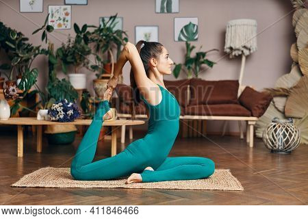 Sporty Woman Doing Yoga Exercise One Legged King Pigeon Pose At Home. Healthy Lifestyle Concept. Eka