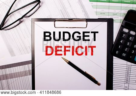 Budget Deficit Is Written On A White Sheet Of Paper, Near The Glasses And The Calculator.