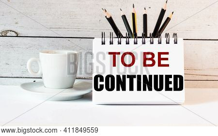The Words To Be Continued Is Written In A White Notepad Near A White Cup Of Coffee On A Light Backgr