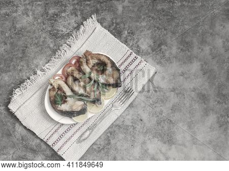 On The Table On A Plate Are Slices Of Fried Carp With Tomatoes And Lemon. Top View, Copy Space