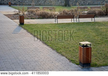 Perennial Flowerbed With Perennials Mulched By Bark On A Park Square With Benches With Wood Paneling
