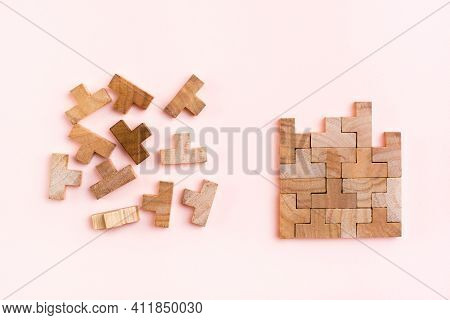 Organization And Order. Wooden Puzzle Pieces Are Stacked Correctly And Chaotically Scattered In Disa