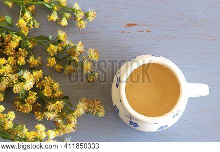 Tea In A Mug On Wood Background With Goldenrod Herb Plant, Solidago Virgaurea On A Blue Background.