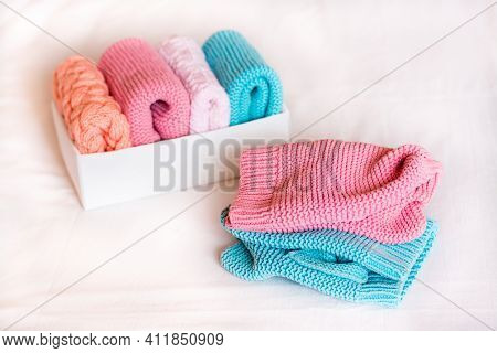Organization And Order. Knitted Clothes Lie Next To A Box Of Neatly Folded Things.