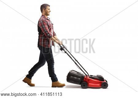 Full length profile shot of a young man working with a lawnmower isolated on white background