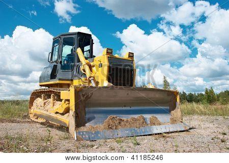 track-type loader bulldozer excavator machine doing earthmoving work at sand quarry