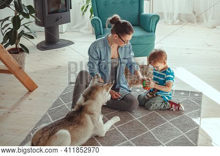 Mom And Child Have Fun And Play With Dog At Home