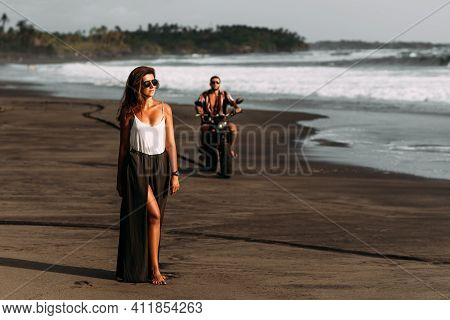 Stylish couple on a motorbike on the beach. A couple on a motorbike meets the sunset. Beautiful couple on a motorbike. Travel on a motorbike. Lovers at sunset. Journey to the island of Bali. Copy space