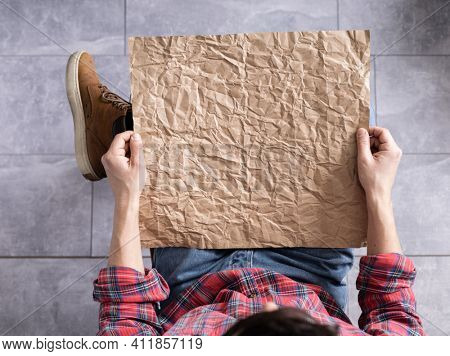Men's hand holding wrinkled old craft paper blank. Male hand and crumpled paper, top view