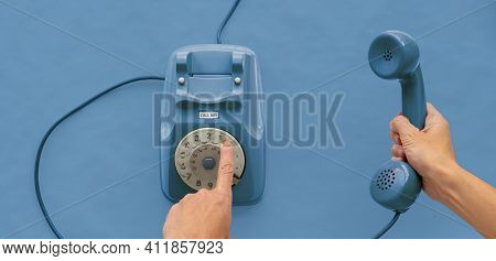 A Blue Vintage Dial Telephone Handset With One Hand And Blue Background.