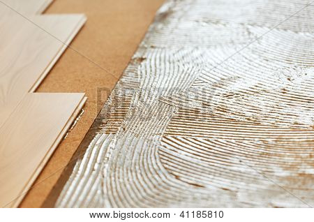 Close-up background of parquet with cork sublayer padding and glue on base during wood flooring