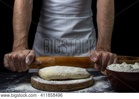 Dough On A Dark Background. The Cook Works With The Dough On A Black Background. The Baker Works Wit