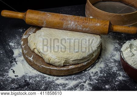 Dough On A Dark Background. Rolling Pin On Home Test On A Black Background. Floured Dough, Tools For