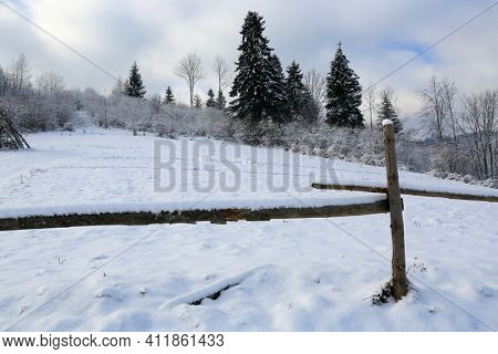 Landscape with wooden fence on snovy meadow. Take it in Ukraine