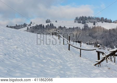 winter scene with wooden fence on meadow edge