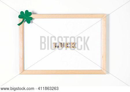 Minimalistic Flatlay For St. Patrick's Day. Shamrock And Frame On White Background. Happy Irish Holi