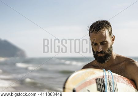 Surfer Holding His Surfboard Walking On The Beach - Hipster Man Training With Surfboard - Lifestyle