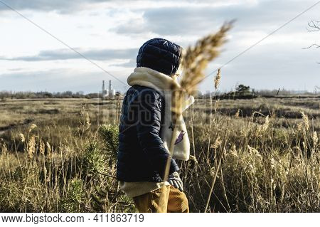 Back View Of A Child Wearing Winter Clothes Walking With Wild Landscape And Factories On The Backgro