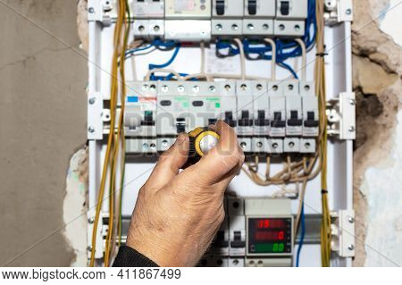 Electrical Switchboard. A Male Electrician Installs A Multifunctional Shield To Control Electricity