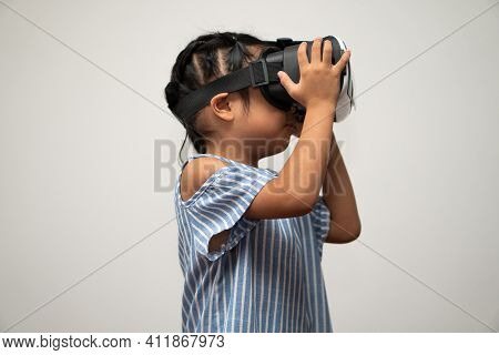 Little Asian Girl Child With Virtual Reality Headset Is Exciting For New Experiencing. Concept Of 3d