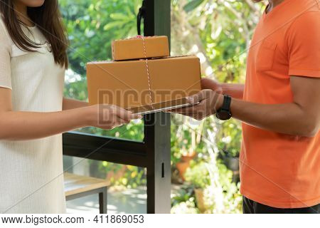 Delivery Service Worker In Uniform Delivering Parcel To Recipient. Woman Signing E-document On Table