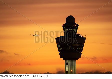 Amsterdam Schiphol International Airport Control Tower With A Plane Landing In The Background During