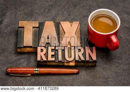 tax return  banner - word abstract in vintage letterpress printing blocks against textured paper with a cup of coffee, business financial concept
