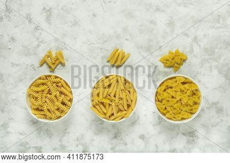 Fusilli, Farfalle And Penne In White Ceramical Bowls On Grey Background With Copy Space, Top View.