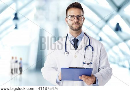Portrait Shot Of Smiling Male Doctor With Stethoscope Around His Neck Standing On The Hopsital Foyer