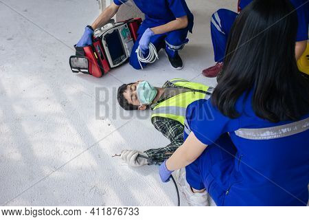 Team Work Medical Emergency Use Automated External Defibrillator (aed) Being Operated On During Help