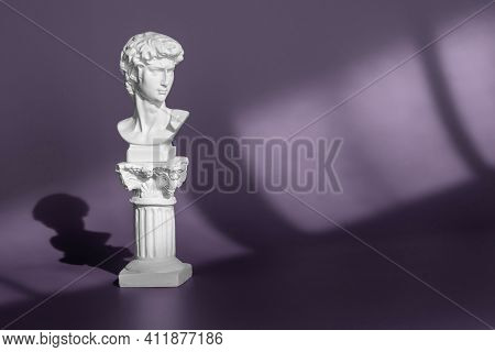 Gypsum Copy Of Ancient Statue Head On Purple Background With Light And Shadow. White Marble Head Of