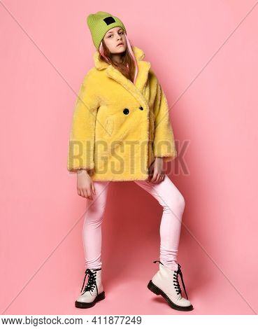 Bright Rebellious Girl Teenager In A Green Hat And A Yellow Fur Coat. Concept Of Childhood Rebellion
